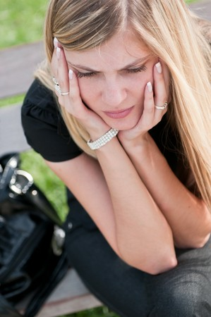 Young worried beautiful woman siting on bench - head in hands photo