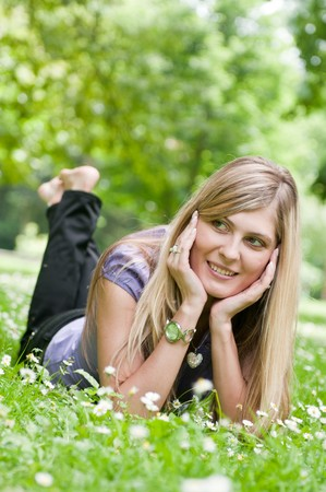 Young smiling woman lying in grass during sunny day (park - outdoors) photo