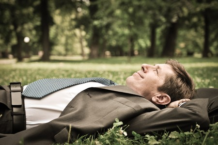 Senior people series - mature business man lying on grass and relaxing in park photo