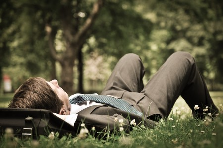 positive thinking: Senior people series - mature business man lying on grass and relaxing in green park