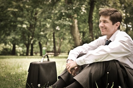 Senior people series - mature business man siting on grass and relaxing in park photo