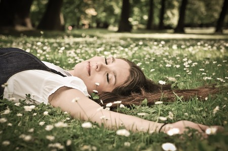 woman lying down: Relaxed young person (teenage girl) lying in grass and flowers with stretched hand - closed eyes Stock Photo