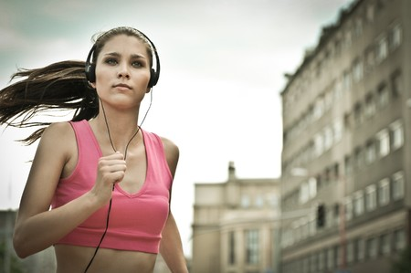 woman running: Person (young beautiful woman) listening music running (jogging) in city street