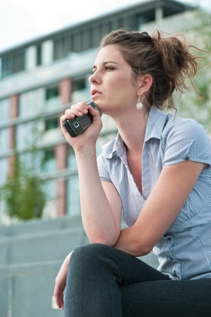 Young worried woman with unhappy expression holding mobile phone - outdoors in urban setting Stock Photo - 7565245
