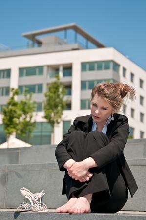 sandalia: Young preocup� el negocio mujer alojados descalzo exterior - zapatos mentir siguiente ella  Foto de archivo