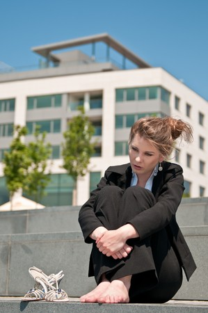 Young worried business woman siting barefoot outdoors - shoes lying next her Stock Photo - 7565266
