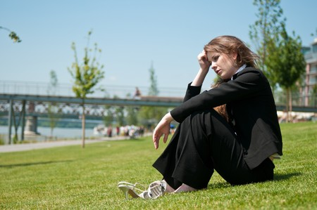 Young worried business woman siting outdoors in grass - head in hand Stock Photo - 7565253