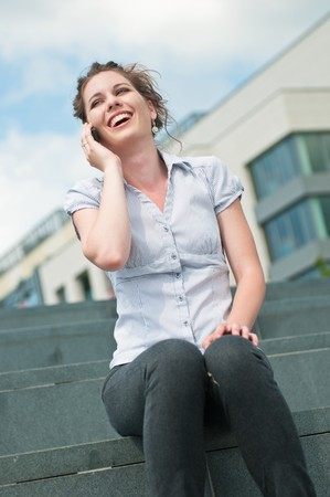 Young beautiful laughing woman calling with mobile phone photo