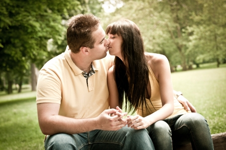 young couple hugging kissing: Young couple in love kissing outdoors - sitting on bench