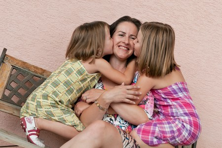 Portrait of children kissing mother with proud and happy expression photo