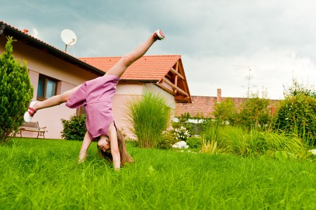 Small girl making cartwheel on garden with family house in background photo