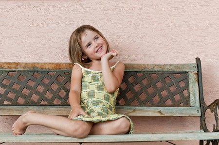 little girl sitting: Outdoors portrait of small cute child - natural smiling expression Stock Photo