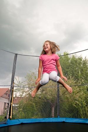 Niño lindo pequeño salto de trampolín - jardín y de la familia casa en segundo plano