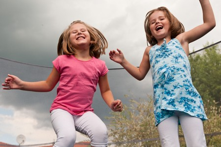 bounce: Small cute children jumping on trampoline - garden and family house in background Stock Photo