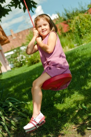 Happy small cute girl swinging on seesaw in garden behind family house photo