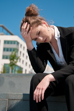 Young worried business woman siting outdoors - head in hand Stock Photo - 7579350