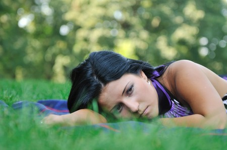 Young sad teenager lying outdoors in grass - detail photo