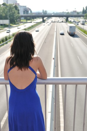 brige: Young woman standing on brige over highway looking on traffic