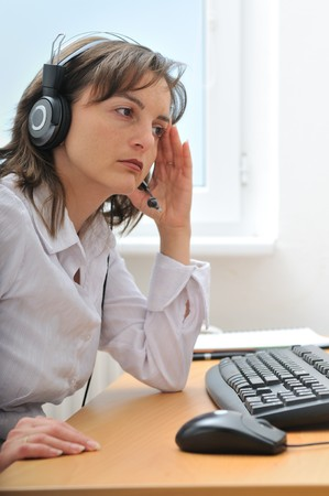Young unhappy tired call center employee with headache sitting at computer on workplace Stock Photo - 7699750