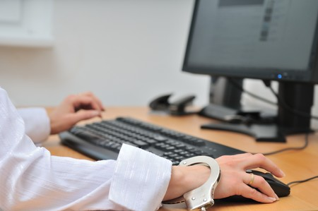 Detail of business person hand tied with handcuffs to workplace, keyboard and monitor in background. Stock Photo - 7698971