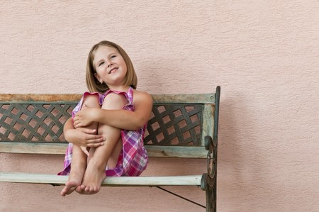 Portrait of cute smiling child sitting on bench and holding her legs Stock Photo - 7699698