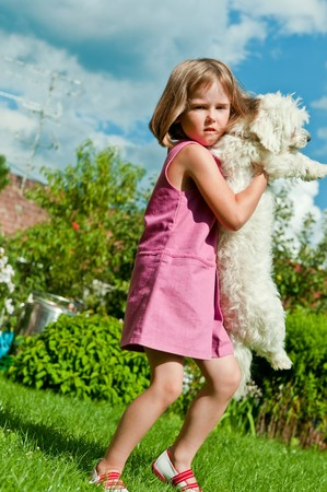 Small cute girl carrying her dog in garden behind family house photo