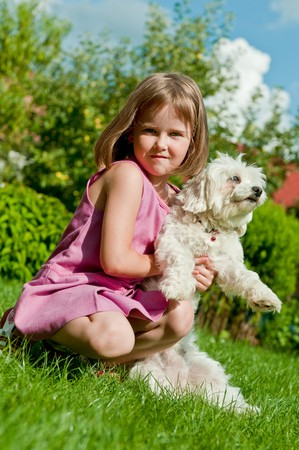 Small cute girl playing with her dog in garden behind family house photo
