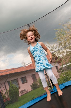Small cute child jumping on trampoline - garden and family house in background photo