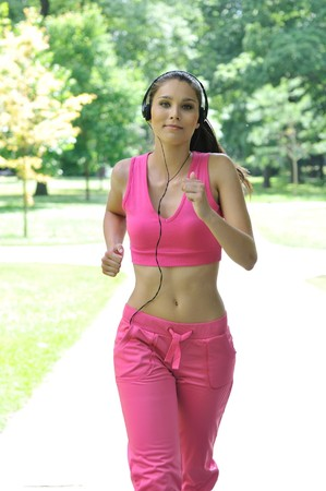 Young person (woman) with headphones listening music running outdoors in park on sunny day Stock Photo