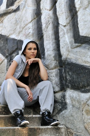 Young person (teenagerl) in hip hop style siting on stairs in front of black and white graffity wall Stock Photo - 7699862