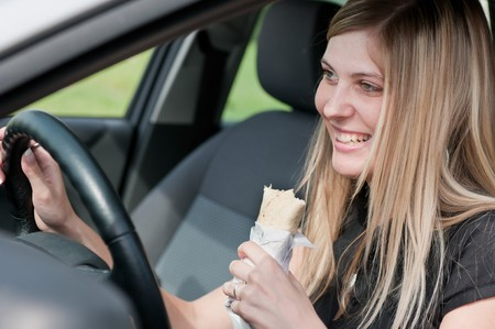 car inside: Young beautiful smiling woman driving car and eating fast food - portrait through side window Stock Photo