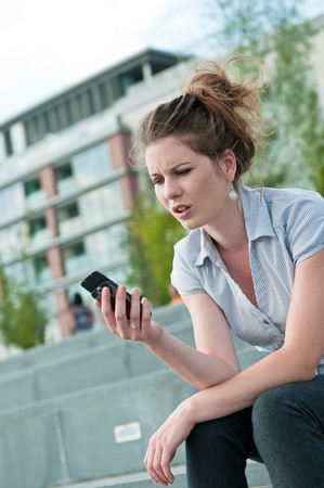 Young worried woman with unhappy expression holding mobile phone - outdoors in urban setting Stock Photo - 7699680