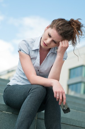 Young worried woman with unhappy expression holding mobile phone - outdoors in urban setting Stock Photo - 7699684
