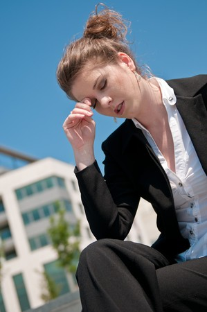 Young depressed business woman siting outdoors - building in background Stock Photo