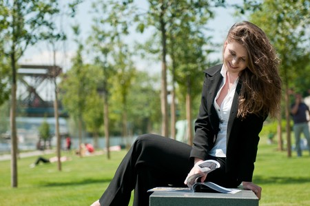 brak: Young business woman sitting outdoors and reading magazine