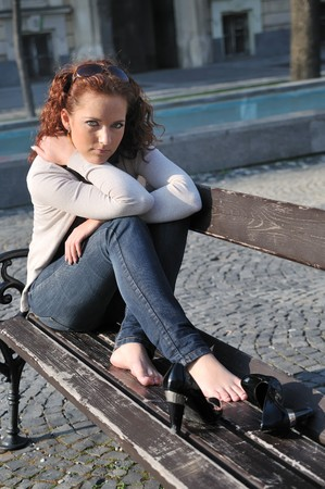 Young serious woman siting on bench in street with sad expression photo