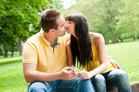 Young couple in love kissing outdoors - sitting on bench