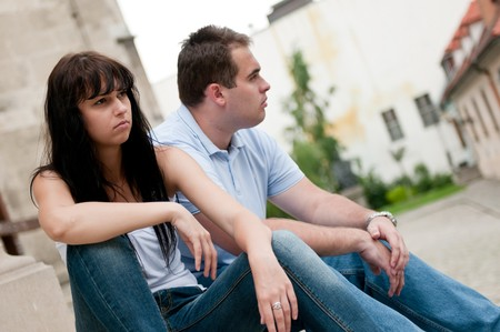 misunderstanding: Young couple sitting outdoors on stairs in misunderstanding Stock Photo