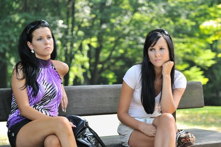 Sad teenage girls siting on bench in park - frendship problems Stock Photo - 7698974
