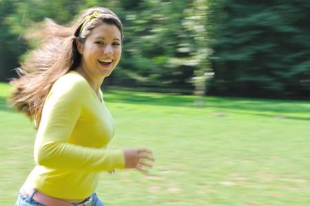 panning shot: Panning shot of teenage girl running in park