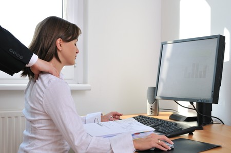 visible: Business working person (woman) behind computer receiving neck massage from colleague (only hands visible)
