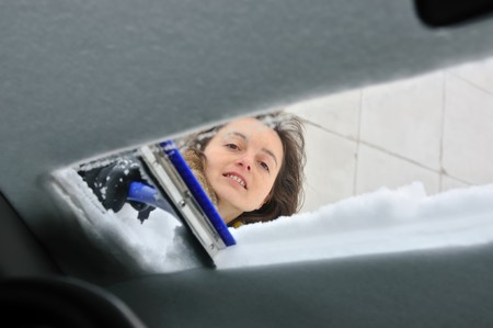 inconvenience: Young smiling woman cleaning car windows from snow in winter season Stock Photo