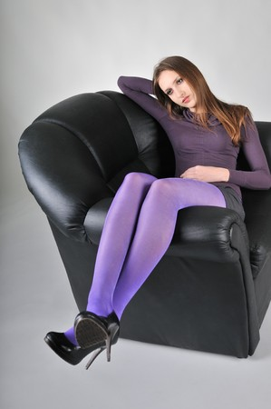 Portrait of young woman with violet pantyhose sitting in big armchair - studio shot photo