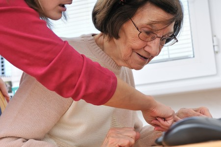 Young woman teaches her grandmother work with computer - senior lifestyle photo