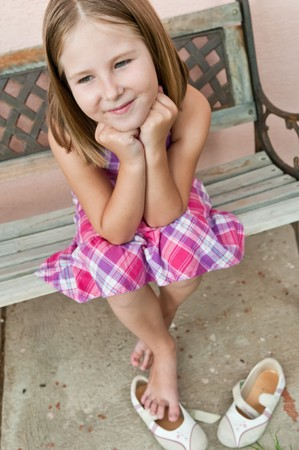 simple girl: Portrait of cute smiling child sitting on bench - wall in background Stock Photo