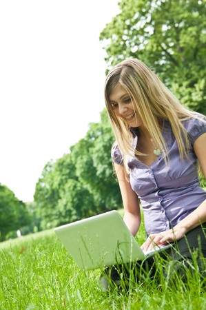 Young blond woman working with netbook outdoors in park on grass Stock Photo - 7807677