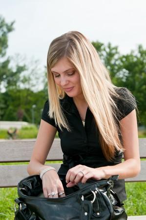 Hermosa rubia joven buscando algo en su bolso de mano grande