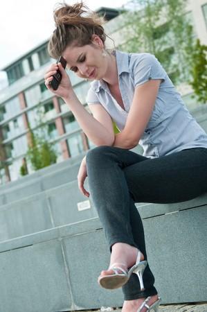 femme inqui�te: Jeune femme inqui?te ? l'expression malheureuse tenant t?l?phone mobile - ? l'ext?rieur dans un cadre urbain