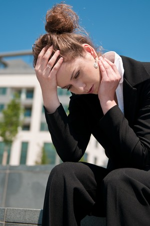 Young worried business woman siting outdoors - head in hand