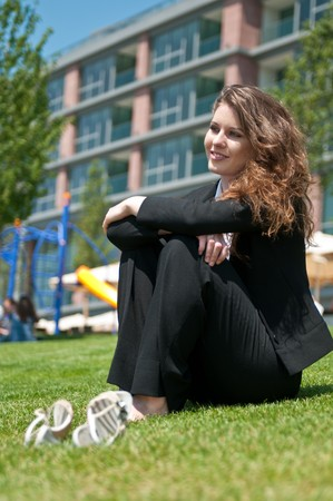 Young cheerful business woman in suit relaxing on grass during lunch break photo